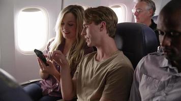 coppia che guarda il cellulare insieme durante un volo in aereo video