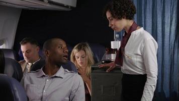 assistente di volo che serve bevande ai passeggeri dell'aereo di linea video