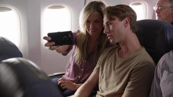 coppia che si fa selfie con il cellulare in aereo video