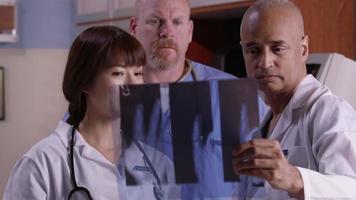 tre läkare tittar över röntgen tillsammans video