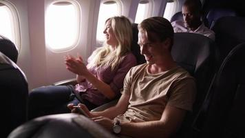 Couple looking at mobile phone together on airplane flight video