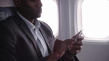 Businessman talking on cell phone on airplane flight video