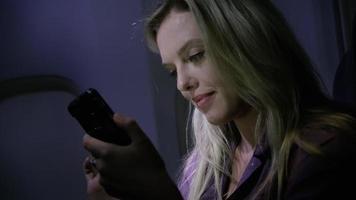primo piano di una giovane donna che usa il cellulare di notte in aereo video