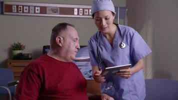 Patient and doctor look at digital tablet together video