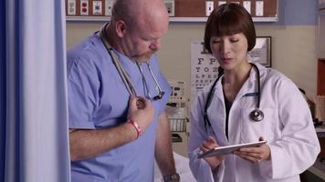 médico e enfermeiro olham para tablet digital juntos video