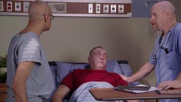 Senior man in hospital bed talks to doctors video