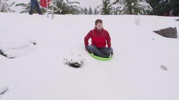 menino descendo uma colina coberta de neve no inverno video