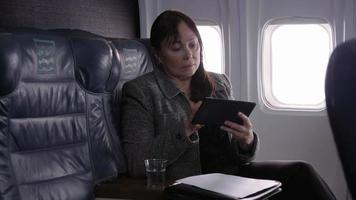 La empresaria mediante tableta digital en avión video