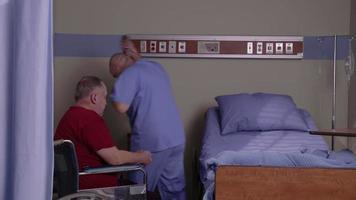 enfermeira ajuda senor homem a sair da cadeira de rodas e ir para a cama do hospital video