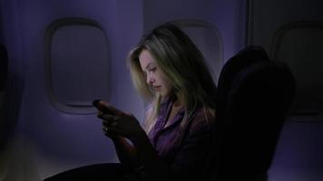 donna che usa il cellulare di notte in aereo video