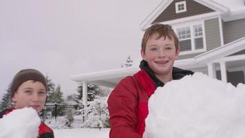 retrato de dois meninos segurando grandes bolas de neve em casa no inverno video