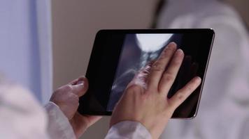 läkare tittar på röntgenstrålar med pekskärmstablett video