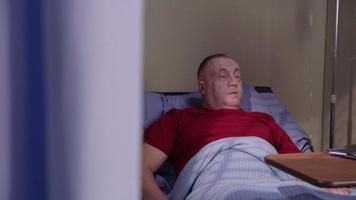 enfermeiro olha para tablet digital com homem sênior na cama de hospital video