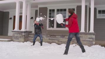 meninos lutando com bola de neve em casa no inverno video