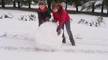 dos niños rodando una bola de nieve en invierno video
