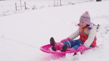 crianças brincando e empurrando trenó na neve do inverno video