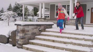 três crianças descendo degraus cheios de neve em casa no inverno video