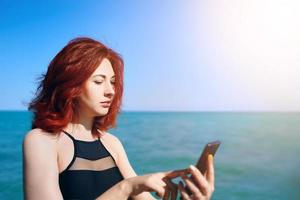 Red haired woman writes message on her mobile phone on the background of the sea sunset photo