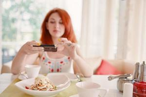 Red haired woman takes photos of salad on smartphone camera