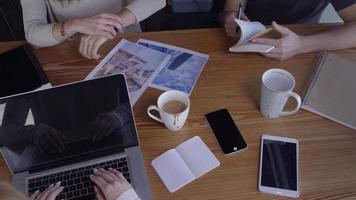 Overhead shot of young business people working together in casual workspace video