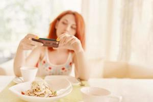 Redhaired woman takes photos of salad on smartphone camera