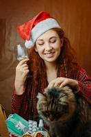 Funny girl in santa hat hold glass of pills and stroke cat photo