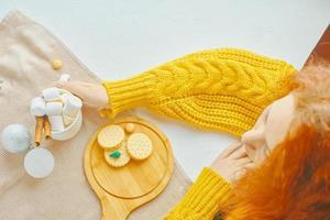 chica pelirroja en suéter caliente con una taza de cacao foto