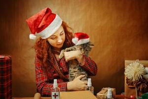 Woman in Santa Claus hat with cat in Christmas hat photo