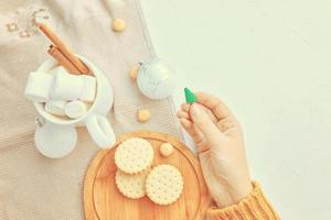 La mujer sostiene una taza de juguete de Navidad de galletas de café y un mantel en la mesa foto