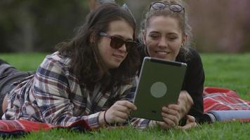 Two young people at park on blanket looking at digital tablet together video