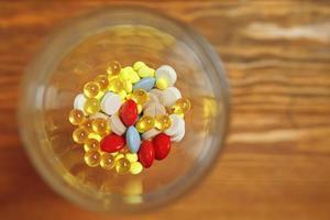 Vista superior del vidrio con vitaminas y pastillas en el interior. foto