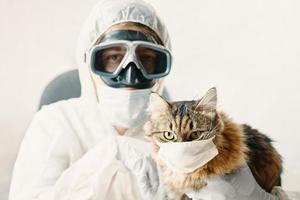 hombre en traje y gato en una máscara médica foto