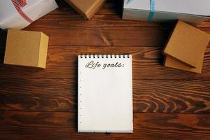 mesa de madera con cajas de regalo, bloc de notas con lista de objetivos de vida foto