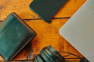 Top view of headphones smartphone and leather wallet on wooden table photo