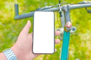 Man trains on bike with smartphone photo
