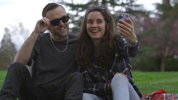 Two young people at park taking selfie together video