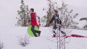 crianças andando na neve com trenós no inverno video