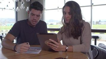 Two young people working together with digital tablet video