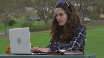 Woman at park on working on laptop computer video