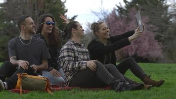 Group of young people at park on blanket taking selfies together video