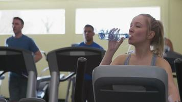 Woman taking drink of water at gym video
