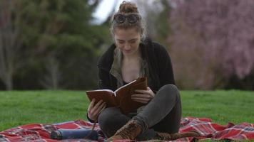 Young woman at park sitting on blanket looking at book video