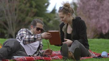 Two young people at park on blanket looking at book together video