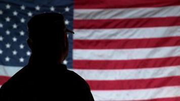 silhouette de soldat saluant avec drapeau américain en arrière-plan video
