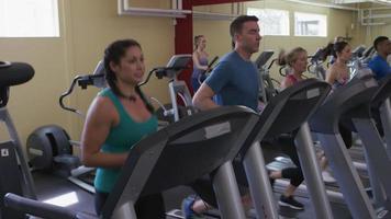gente en el gimnasio corriendo en cintas de correr video