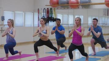 Group of people doing yoga at studio video