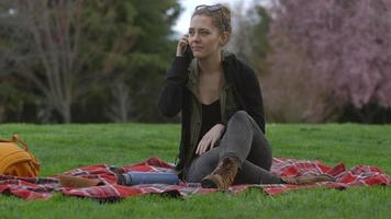 Young woman at park sitting on blanket talking on cell phone video