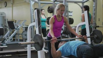 Man and woman at gym lifting weights video