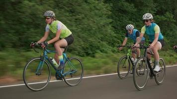Tracking shot of a group of cyclists on country road.  Fully released for commercial use. video