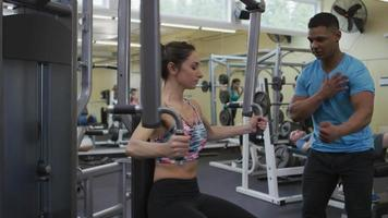 Young woman working out with trainer at gym video